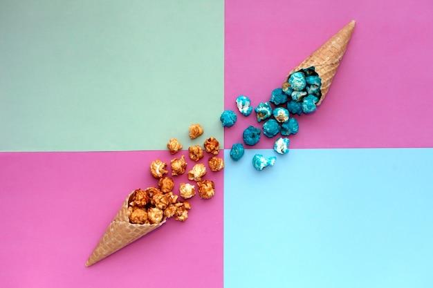 파스텔 화려한 배경의 와플 아이스크림 콘에서 팝콘이 쏟아져 나옵니다. 원뿔 풍요의 뿔에 있는 파란색과 카라멜 팝콘 위쪽은 밝은 힙스터 배경을 볼 수 있습니다. 패스트 푸드.
