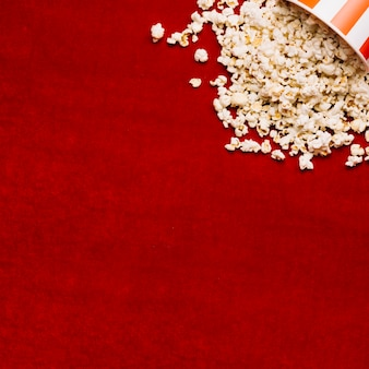Popcorn spilled from bucket on red cloth