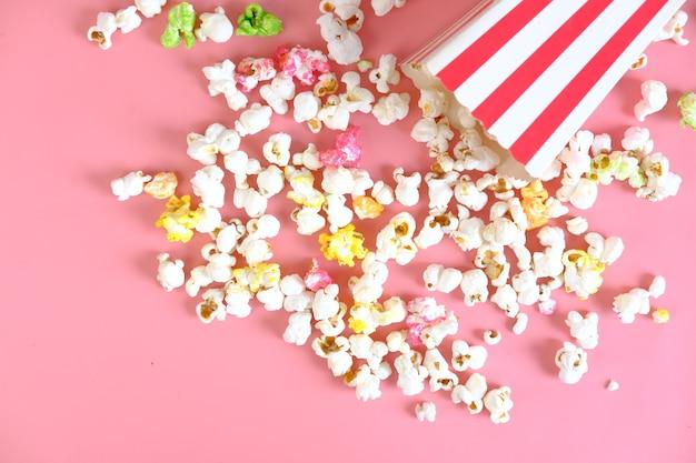 Попкорн выливается из контейнера на розовом
