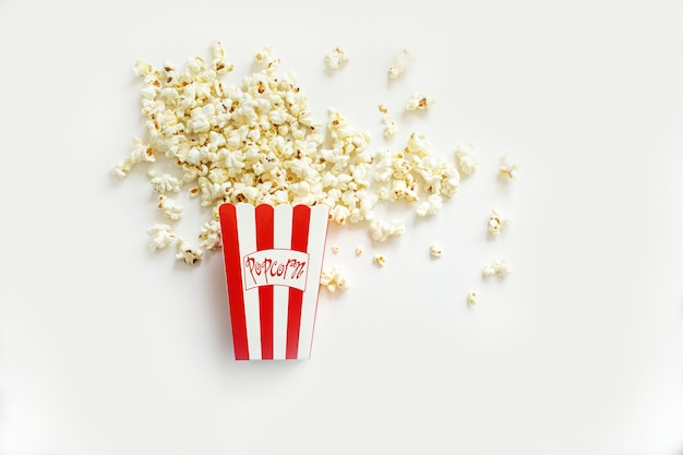 Popcorn spilling out of a red and white striped paper cup