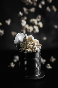 Popcorn in a steel tin, falling popcorn on dark background, moody photo