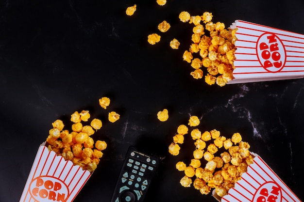 Popcorn in striped boxes spilled on black surface with remote control