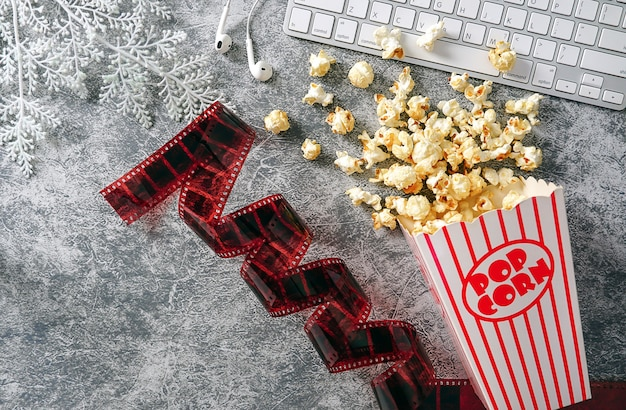 Popcorn in striped buckets and film strips with computer keyboard on gray cement background