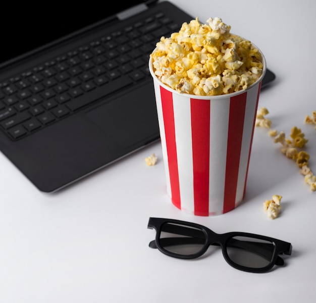 Popcorn in striped red bucket, 3d glasses, and laptop playing movie.