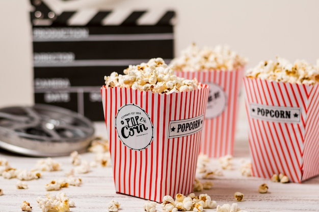 Popcorn in the three striped bucket with film reel and clapperboard on wooden board