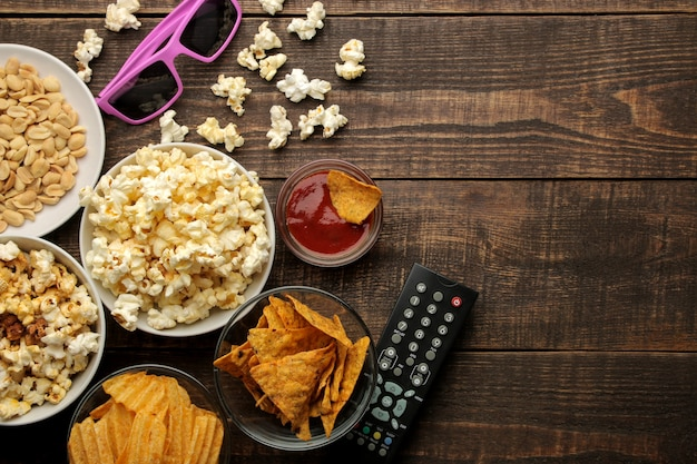 Popcorn and various snacks, 3d glasses, tv remote on a brown wooden background. concept of watching movies at home. view from above