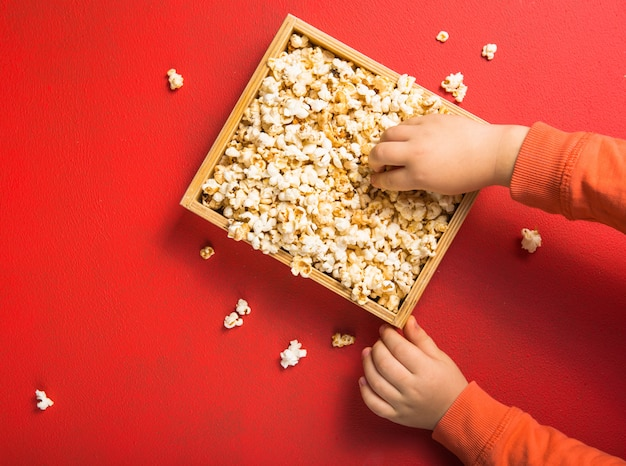 Popcorn viewed from above on red background. child eating popcorn. human hand. cinema snack concept. the food for watching a movie and entertainment. copy space for text, flat lay.
