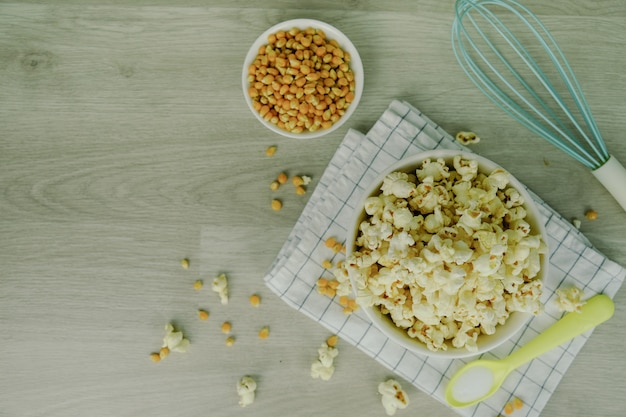 Popcorn in white bowl with pastel spoon, salt, hand mixer and corn seeds on wood background.