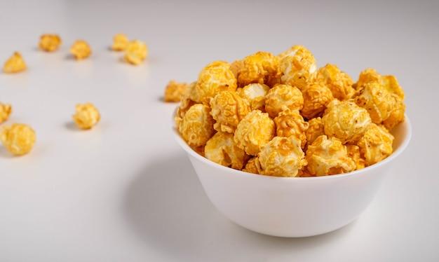 Попкорн со вкусом карамели в белой тарелке на белой поверхности
