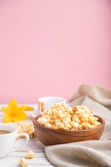 Попкорн с карамелью в деревянной миске и чашка кофе на бело-розовой поверхности и льняной ткани