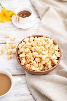 Popcorn with caramel in wooden bowl and a cup of coffee