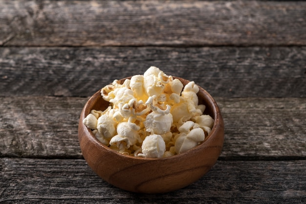 Popcorn in a wooden bowl in rustic style. text space