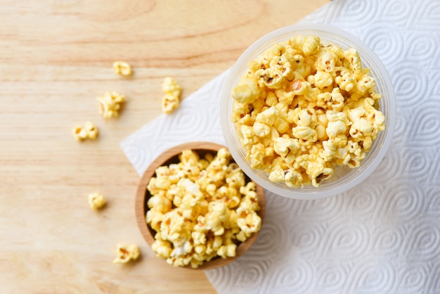 Popcorn in wooden cup bowl and wood backgroubd top view / sweet butter popcorn salt