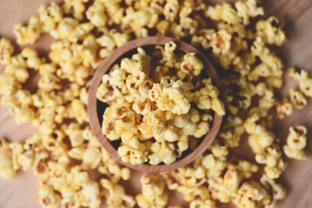 Popcorn in wooden cup bowl and wood