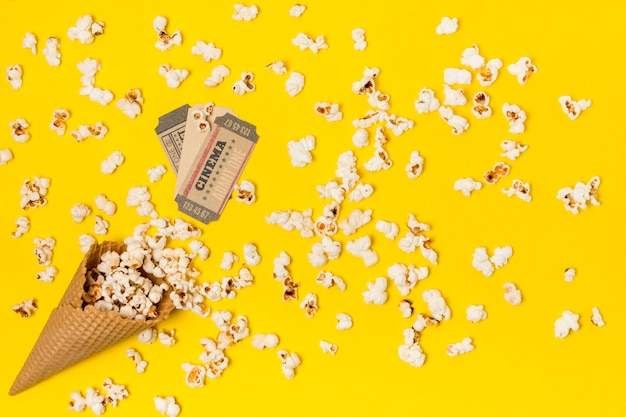 Popcorns spilled from the waffle cone with cinema ticket