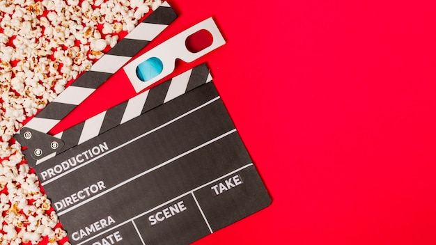 Popcorns with clapperboard and 3d glasses on red backdrop