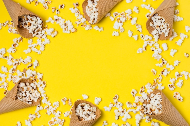 Popcorns with waffle cones on yellow background with space for writing the text
