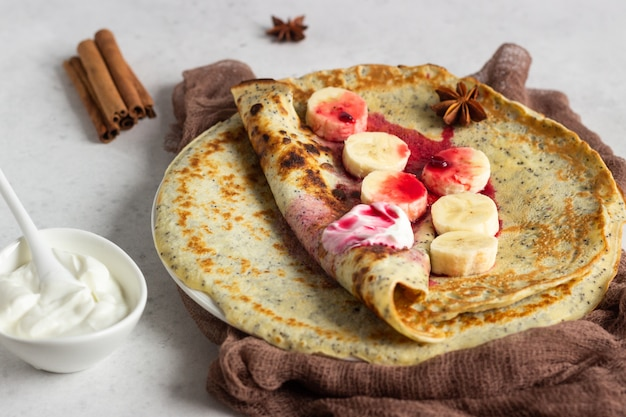 Poppy seed pancakes with natural yogurt, banana and cherry sauce with spices