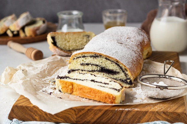 Poppy seed roll or strudel on wooden board sprinkled with powdered sugar.