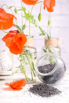 Poppy seeds on a white background and flowers