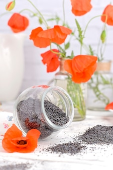 Poppy seeds on a white background and flowers.