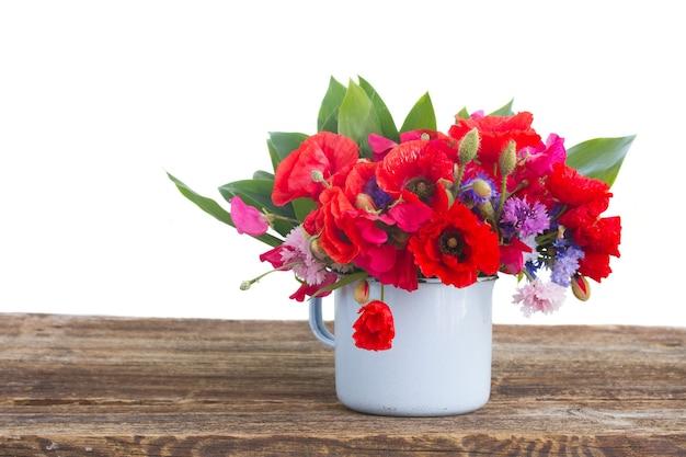 隔離されたテーブルの上のポーのポピー、スイートピー、トウモロコシの花