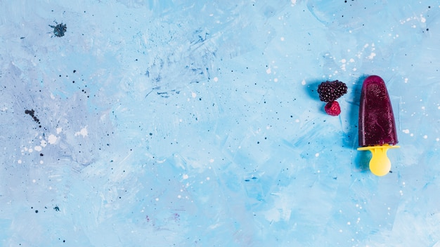 Popsicle and berries on blue background