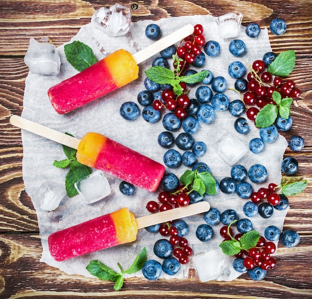 Popsicles with red currants and blueberries on a wooden