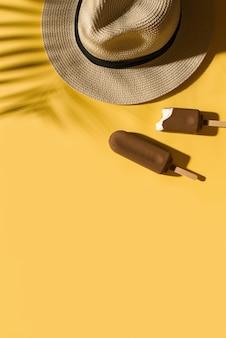Мороженое popside и шляпа на ярко-желтом фоне с тенью тропических листьев, креативной пастелью, копией пространства