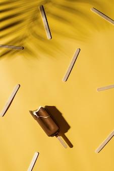 Мороженое popside на ярко-желтом фоне с тенью тропических листьев, креативной пастелью, копией пространства