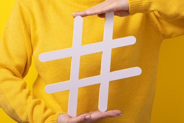 Popular blog posts, trendy content, hands holding hashtag sign over yellow background