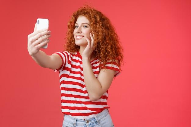 Популярная веселая симпатичная стильная женщина-блогер с рыжей вьющейся прической чувствует себя довольно самоуверенно, принимая селфи поднятой рукой, держа смартфон, позируя глупо милой телефонной камерой на красном фоне.