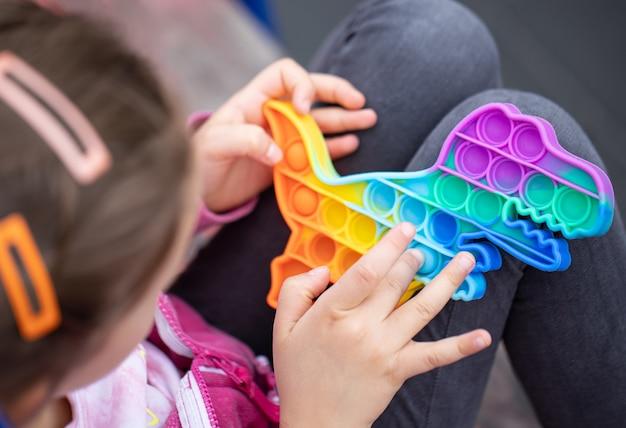Il popolare giocattolo colorato antistress a forma di drago si agita spingendolo nelle mani di un bambino
