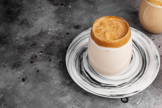 Popular drink korean dargon coffee made of instant coffee, sugar, hot water and milk in glass on grey space. copy space