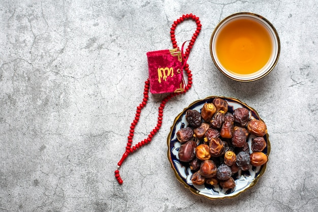 Популярная еда во время ифтара сухие финики каран четки на бетонном фоне вид сверху плоский лежал мусульманский хо ...