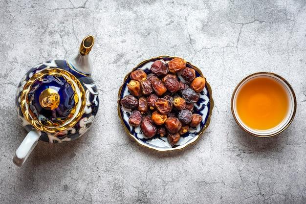 Популярная еда во время ифтара. сухие финики. чайник с черным чаем на бетонном фоне. вид сверху плоский ...