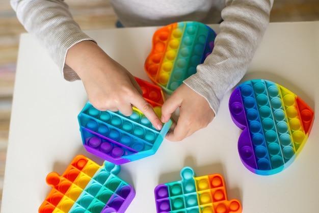 인기 게임 팝 아이가 미세 운동 기술 개발을 위해 유연한 실리콘 장난감을 들고 있습니다.