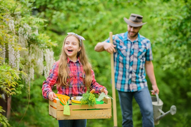 Popular in garden care. planting flowers. transplanting vegetables from nursery gardening center. plant veggies. planting season. family dad and daughter little girl planting plants. day at farm.