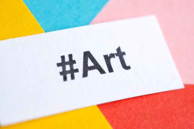 Popular hashtag 'art' printed on white sheet of paper on multicolored paper