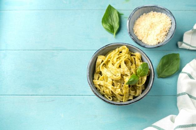 Popular italian pasta with pesto sauce, close-up on blue wood