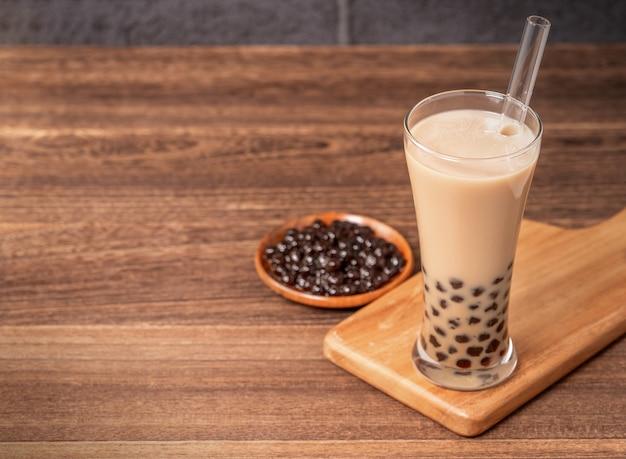 Популярный тайваньский напиток - пузырьковый чай с молоком с жемчужным шаром тапиоки в стакане и соломинке, деревянный стол на фоне серого кирпича, крупный план, копия пространства