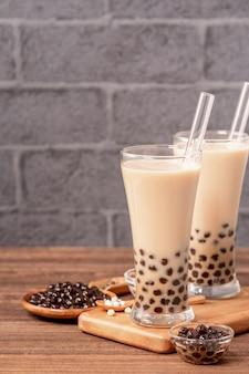 人気の台湾の飲み物タピオカパールボールとグラスとストローの木製テーブルでバブルミルクティーを飲む