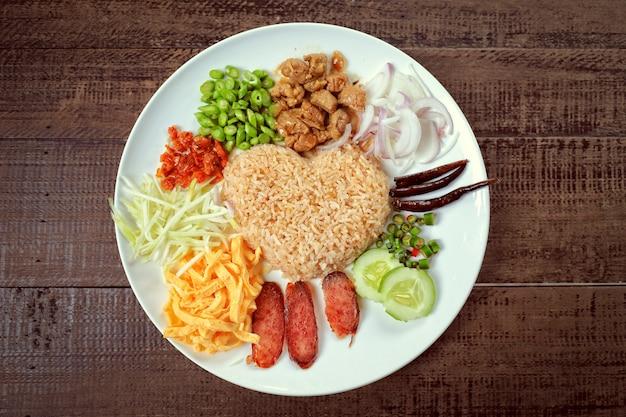Популярная местная тайская еда, жареный рис с креветочной пастой, подается с овощами, нарезанным яйцом и пряными ингредиентами, разнообразные овощи.