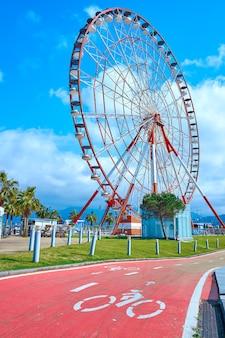 Популярные туристические места в городе батуми. колесо обозрения на набережной. выделенная дорога для велосипедистов.