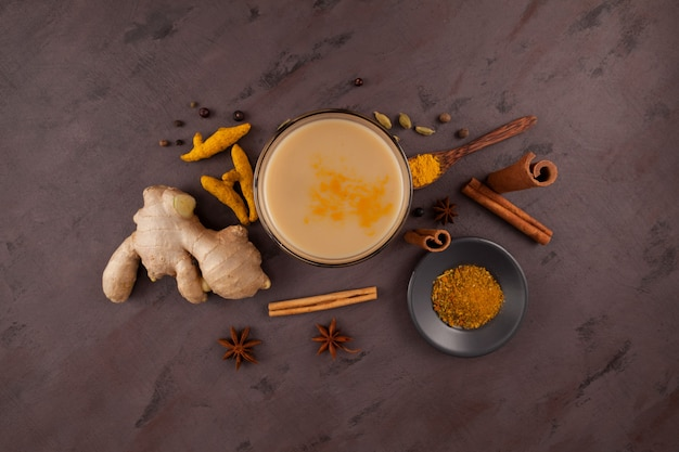 Popular traditional indianasian drink masala chai or spicy herb tea with all the ingredients on brown