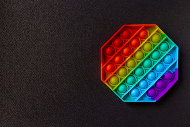 Популярная модная игрушка fidget push pop it на черном фоне копировальное пространство