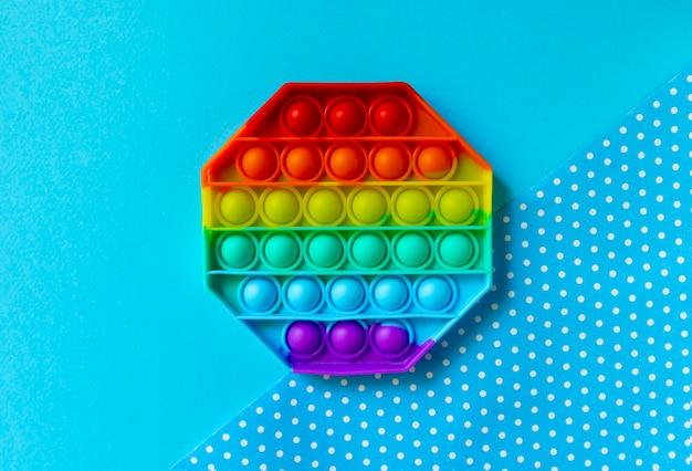 Популярная модная игрушка fidget push pop it на синем фоне
