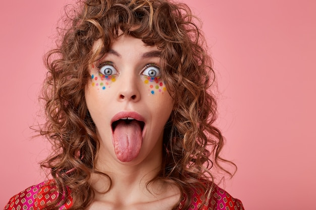 Poratrait of young curly blue-eyed woman with multicolored dots on her face looking with wide eyes opened and sticking out her tongue, isolated