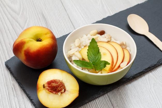 수수 죽, 캐슈넛, 아몬드, 신선한 복숭아 한 개 반, 돌판에 나무 숟가락을 넣은 도자기 그릇. 신선한 과일을 곁들인 비건 글루텐 프리 수수 샐러드.