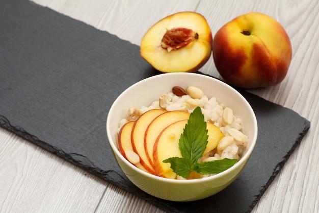수수 죽, 신선한 복숭아, 캐슈 너트, 아몬드, 민트 잎이 있는 도자기 그릇은 검은색 돌판과 회색 탁자에 있습니다. 신선한 과일을 곁들인 비건 글루텐 프리 수수 샐러드. 평면도.
